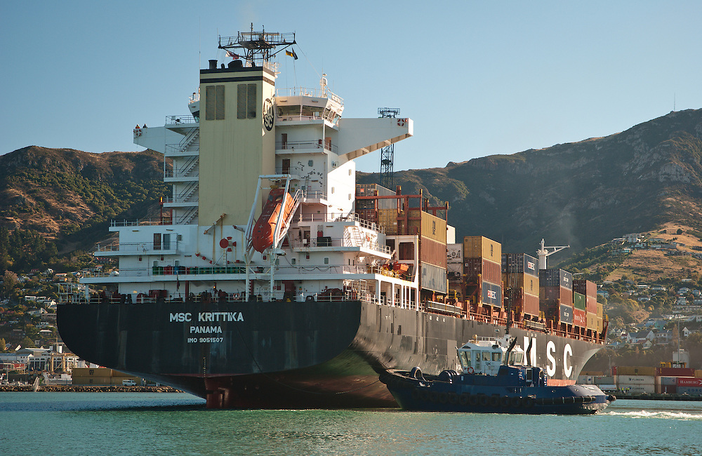 A tugboat manoeuvres container vessel MSC Krittika into port at Lyttelton, New Zelanad, with the Port Hills in the background