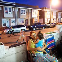 Teens race past as Mary Perez hugs her 1 year old daughter, Isabella, with a front porch view of the Trump casino, in Atlantic City, NJ on September 4, 2014.  Four casinos have already or will be closing in the near future, including Trump Plaza on September 16, resulting in the loss of thousands of jobs.