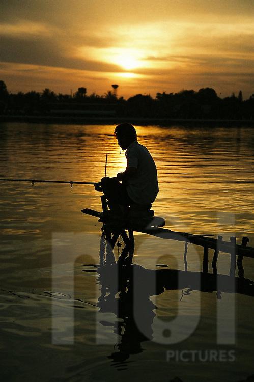 Fisherman on Tay Ho (west lake) by sunset. Hanoi