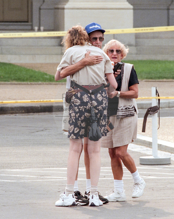 Tourists who witnessed a shooting at the US Capitol Building hug July 24, 1998 in Washington, DC. Two US Capitol police officers were killed in the incident, one person wounded and the lone gunmen was wounded and taken into custody.