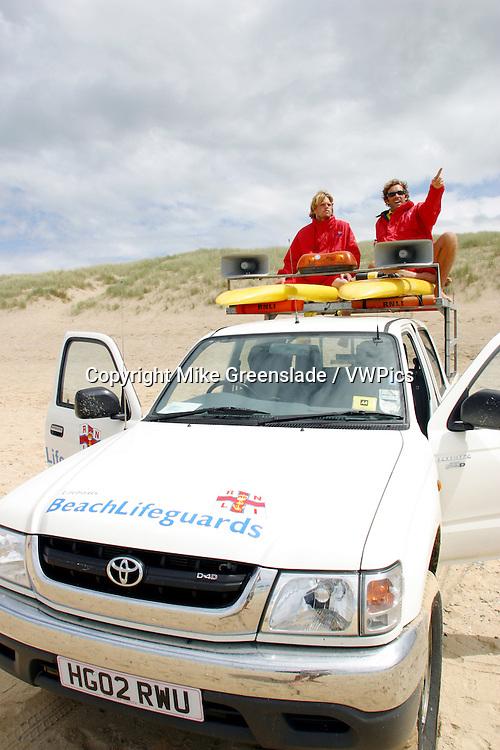 RNLI Beach Lifeguards on patrol, Holywell Bay, Cornwall, UK