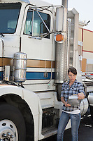 Woman looking at clipboard while standing by flatbed truck