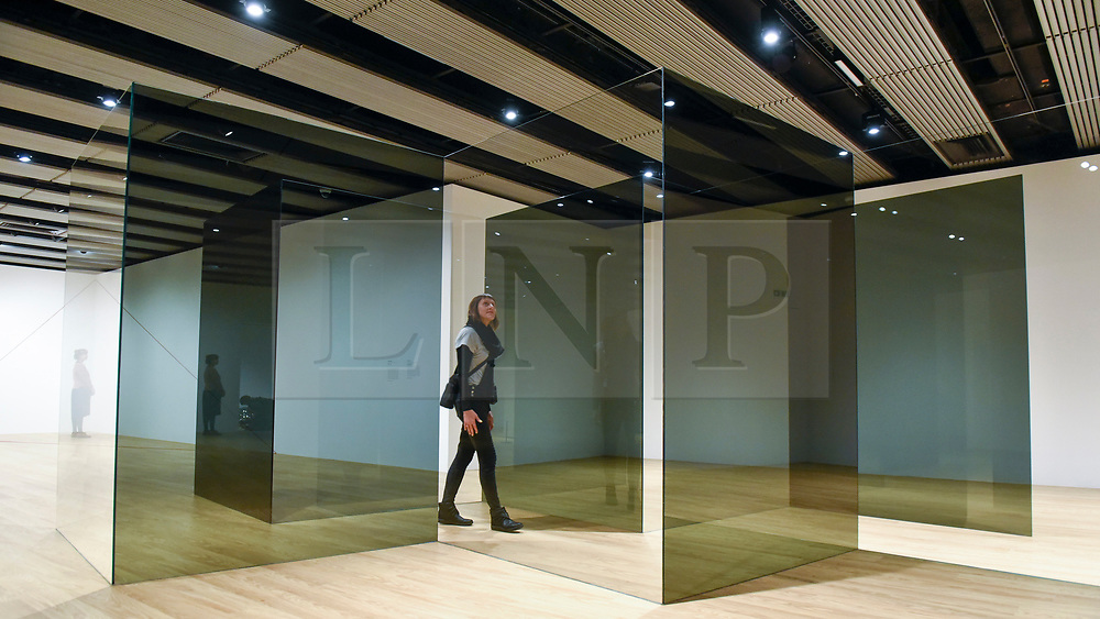"""© Licensed to London News Pictures. 25/09/2018. LONDON, UK. A gallery staff member walk through """"Standing Walls"""", 1969/2016 by Larry Bell. Preview of """"Space Shifters"""" at the Hayward Gallery, an exhibition which features artworks by 20 leading international artists that disrupt the visitor's sense of space and alter their perception of their surroundings.  The show runs 26 September to 6 January 2019.  Photo credit: Stephen Chung/LNP"""
