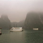 Early morning mist surrounds tourist Junks in Ha Long Bay, Vietnam. The bay consists of a dense cluster of 1,969 limestone monolithic islands. Ha Long Bay, is a UNESCO World Heritage Site, and a popular tourist destination. Ha Long, Bay, Vietnam. Photo Tim Clayton