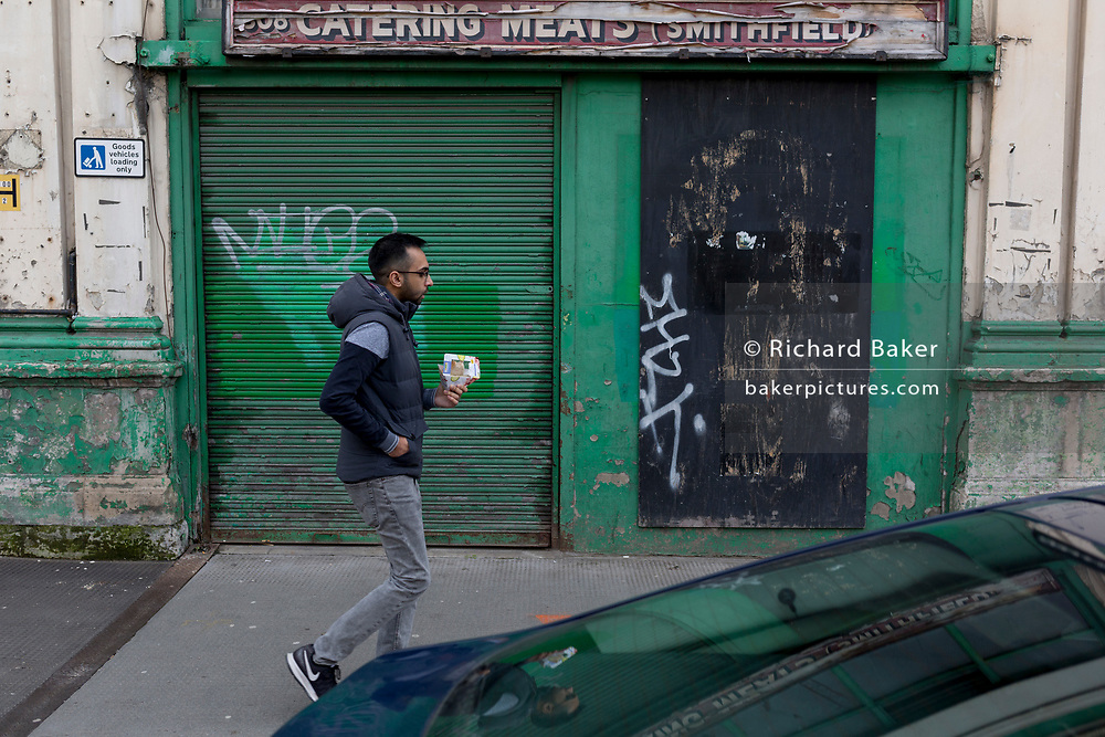 A lunchtime Londoner passes a closed butcher business in the former Smithfield meat market that is awaiting future redevelopment, on 20th November 2019, at Smithfield in the City of London, England. In March 2015, the Museum of London revealed plans to vacate its Barbican site and move into the General Market Building. The cost of the move is estimated to be in the region of £70 million and, if funding can be achieved, would be complete by 2021. There has been a market on this location since the Bartholomew Fair was established in 1133 by Augustinian friars.