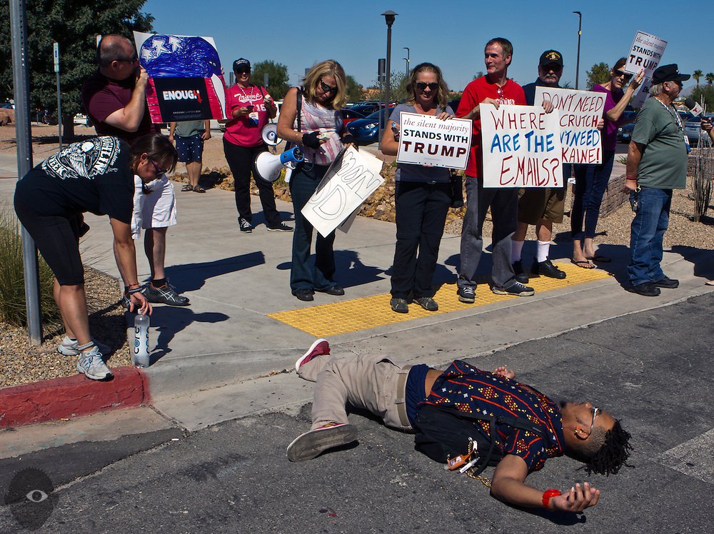 A supporter for Donald Trump throws himself on the ground for effect as they protest outside as President Bill Clinton campaigns on behalf of Hillary Clinton at her previously scheduled event at the College of Southern Nevada on Wednesday, Sept. 14, 2016.  L.E. Baskow