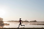 Young woman running by lake Manitoba, Canada, early morning fog on the lake.