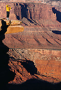 Standing on a rock overhang, photographer Peter Ginter from Germany shots a photo at Dead Horse Point, Utah. MODEL RELEASED. USA.