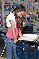 School girl reading book at desk in classroom