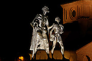 """Low angle view of statue of Lazarillo de Tormes leading the blind man, Salamanca, Spain, pictured on December 19, 2010 at night, flodlit. The novella, Lazarillo de Tormes, published anonymously in 1554, is credited with the founding of the picaresque literary genre. Salamanca, an important Spanish University city, is known as La Ciudad Dorada (""""The golden city"""") because of the unique golden colour of its Renaissance sandstone buildings. Founded in 1218 its University is still one of the most important in Spain. Around it the Old Town is a UNESCO World Heritage Site. Picture by Manuel Cohen"""