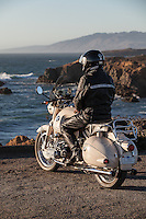 Rider in black leather sitting on a 1960s BMW R60US motorcycle (PR) overlooking the Pacific Ocean in Sonoma County California.