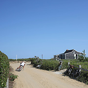 A beach goer leaves Cisco Beach, Nantucket, on her bike. Nantucket Island, Massachusetts, USA. Photo Tim Clayton