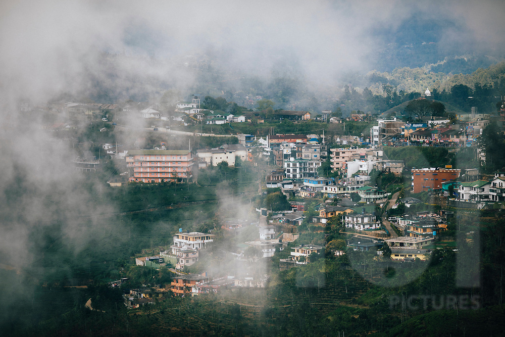 Mist rolls over the mountains into the town of Hapatule, Sri Lanka, Asia