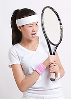 Portrait of young Asian woman with tennis racket winking against white background