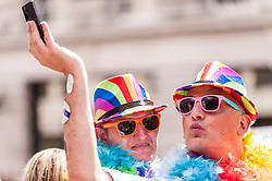 © Licensed to London News Pictures. 27/06/2015. Trafalgar Square, London, UK. A couple pose as they watch participants take part in the annual Pride parade in London, one of the world's largest LGBT+ events.  Hundred of thousands of people gathered to watch the events on a hot summer's afternoon. Photo credit : Stephen Chung/LNP