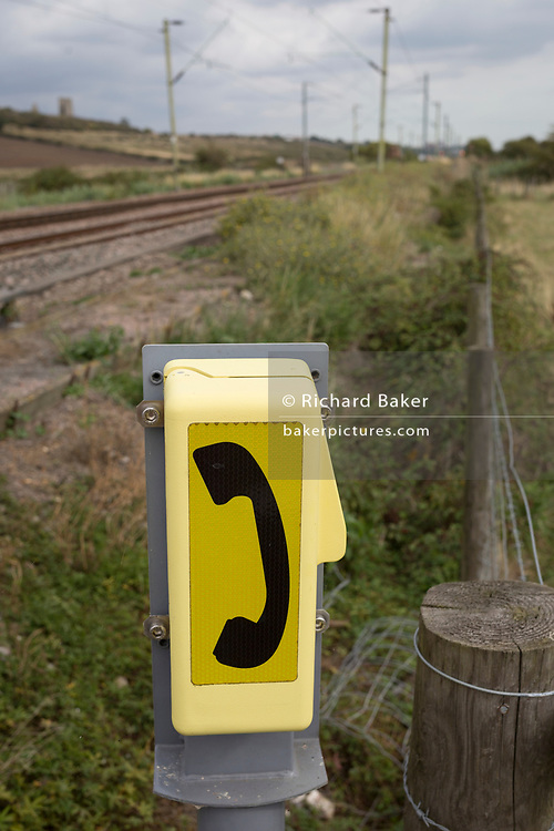 A detail of an emergency Network Rail railway phone at a rail crossing for approaching trains whose route takes them across agricultural marshland near Hadleigh Castle, on 10th September 2019, in Leigh-on-Sea, Essex, England.