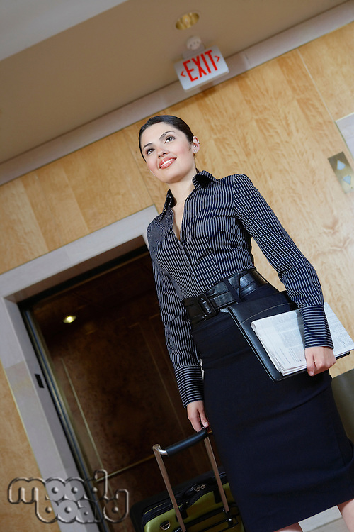 Business woman pulling trolley by elevator