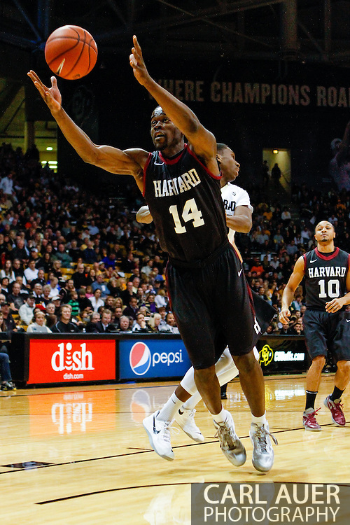 November 24th, 2013:  Harvard Crimson junior forward Steve Moundou-Missi (14) grabs a rebound off of a missed Colorado free throw in the first half of the NCAA Basketball game between the Harvard Crimson and the University of Colorado Buffaloes at the Coors Events Center in Boulder, Colorado
