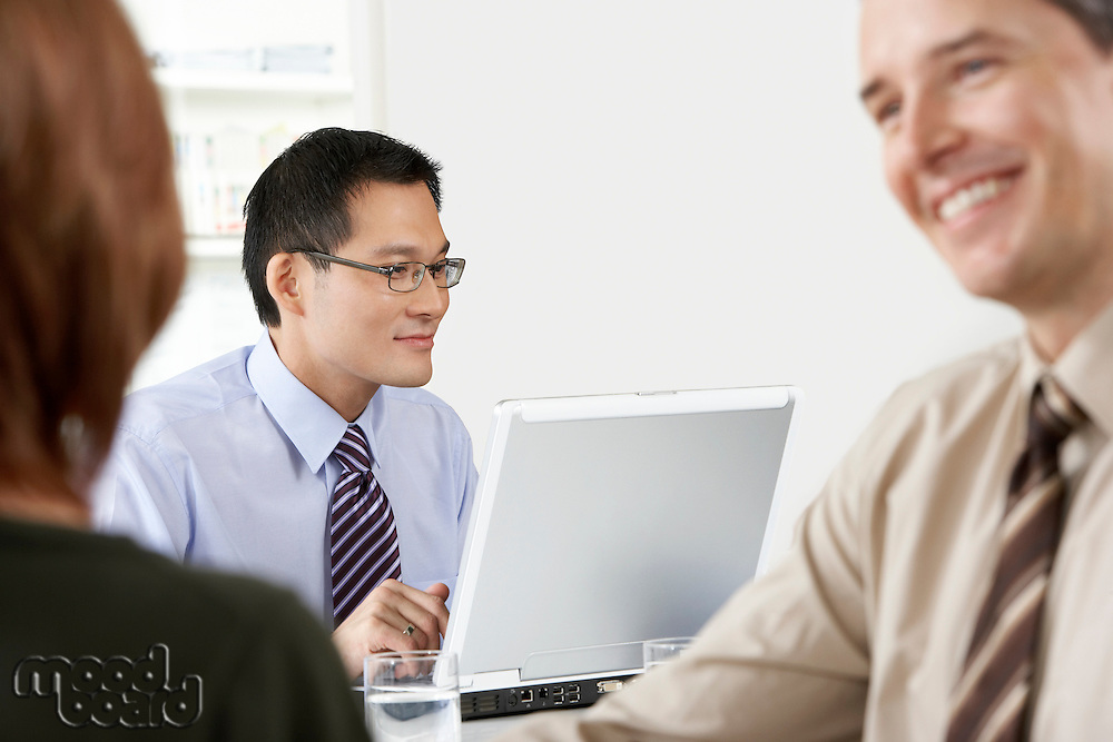 Businessman using laptop businesspeople conferring at office desk