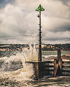 Waves crashing onthe harbour marker at Axmouth