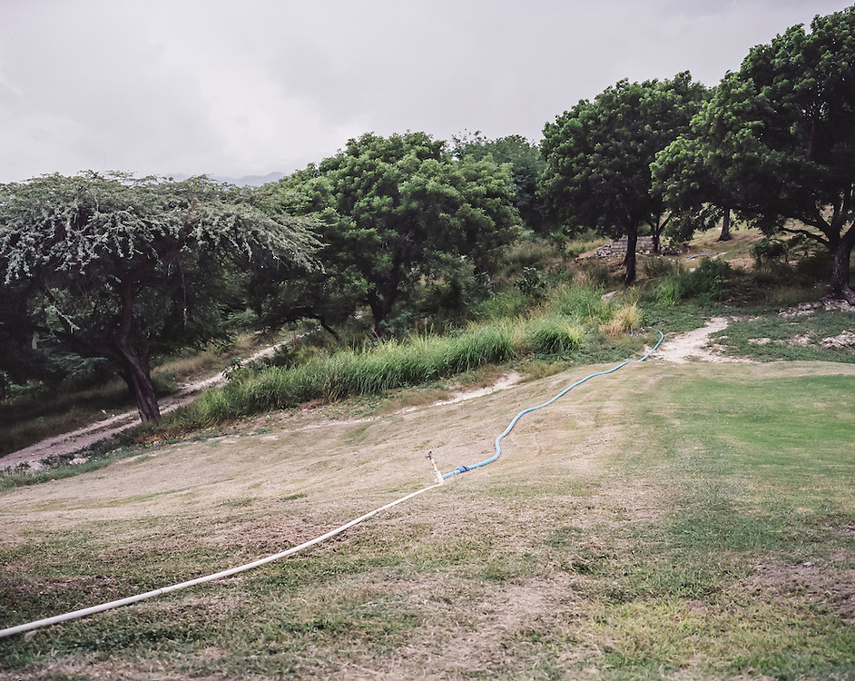A hose irrigates the Petionville Club golf course on Sunday, December 14, 2014 in Port-au-Prince, Haiti. Following the 2010 earthquake, the golf course turned into a tent city that housed tens of thousands of people and was famously managed by actor Sean Penn, but they were recently relocated and the land reverted to private use.