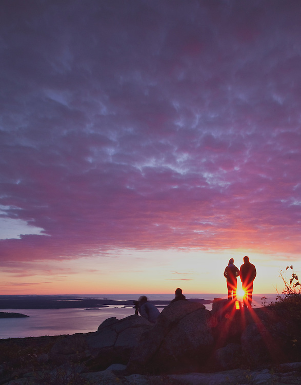 For much of the year, Cadillac Mountain in Acadia National Park, Maine is the first to receive the rays of the morning sun. No visit to the park, when the road is passable, is complete without watching the sunrise from the summit. Here, visitors gather to enjoy nature's light show.