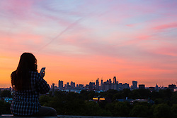 London, August 16 2017 . A woman admires the view of the city skyline as London wakes up to a glorious sunrise © Paul Davey.