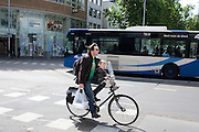 Een man fietst met een kind voorop door Utrecht.<br /> <br /> A man is cycling with a child on his bike.