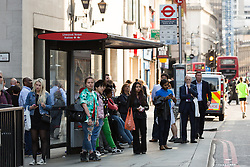 © Licensed to London News Pictures. 08/07/2015. London, UK. City workers waiting for a bus near Liverpool Street station in London. London transport workers begin strike action tonight, which will continue tomorrow. Photo credit : Vickie Flores/LNP