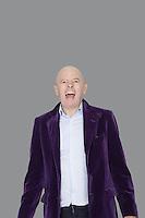 Portrait of screaming senior man over gray background
