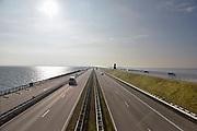 Nederland, the Netherlands, Kornwerderzand, 22-2-2018 De Afsluitdijk zal de komende jaren aanpassingen krijgen om de verwachte zeespiegelstijging en extreem weer het hoofd te kunnen bieden . Het Vlietermonument bevindt zich bij de Vlieter, de plaats waar in 1932 de Afsluitdijk werd gesloten. Het is een monument in de vorm van een uitkijktoren, ontworpen door architect Willem Dudok. De toren is in 1933 gebouwd . Het standbeeld van ingenieur Lely in de verte .Foto: Flip Franssen