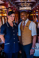 A waitress and waiter in the pillared pre-1940s dining car on the luxury Rovos Rail train between Pretoria and Cape Town, South Africa.