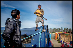 October 27, 2016 - Calais, France - Afghan refugee plays guitar on top a tent among the remains of the migrant camp as refugees start to leave the Calais Jungle migrant camp the day after it caught fire and the French police closed it down. (Credit Image: © Andrew Parsons/i-Images via ZUMA Wire)