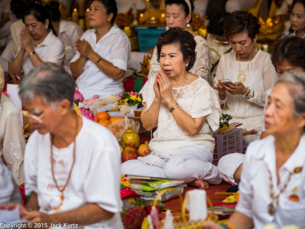 12 OCTOBER 2015 - BANGKOK, THAILAND:   People pray at Wat Mangkon Kamlawat, a large Chinese temple in Bangkok, on the first day of the Vegetarian Festival in Bangkok's Chinatown. The Vegetarian Festival is celebrated throughout Thailand. It is the Thai version of the The Nine Emperor Gods Festival, a nine-day Taoist celebration beginning on the eve of 9th lunar month of the Chinese calendar. During a period of nine days, those who are participating in the festival dress all in white and abstain from eating meat, poultry, seafood, and dairy products. Vendors and proprietors of restaurants indicate that vegetarian food is for sale by putting a yellow flag out with Thai characters for meatless written on it in red.    PHOTO BY JACK KURTZ