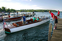 """Kevin Buttermore throws a line from a 1910 Goodhue and Hawkins 36' Laker """"Keen Kutter"""" owned by Dick and Patricia Hopgood as they arrive at the docks in Wolfeboro, NH for the annual antique boat show.  ©2018 Karen Bobotas Photographer"""
