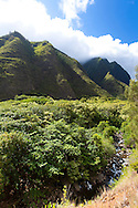 Maui, Hawaii. Iao Valley is a lush, stream-cut valley in West Maui, Hawaii, west of Wailuku.  Because of its natural beauty and historical significance, it has become a popular tourist location.The state park is located on 6.2 acres at the end of Iao Valley Road (Highway 32). The Iao Needle (K?kaemoku) is a famous landmark in the state park, a vegetation-covered lava remnant rising 1,200 feet from the valley floor. The needle is surrounded by the cliffs of the West Maui Mountains, an extinct volcano.
