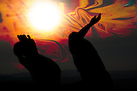 apocalypse, surrealistic representation.Hands to burning sky background with sun and red shades