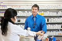 Happy mature man buying pills from female employee in drugstore