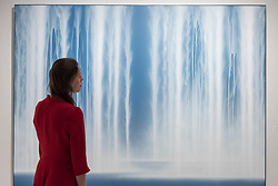 """© Licensed to London News Pictures. 28/06/2018. LONDON, UK. A visitor views """"Waterfall"""", 2014, by Hiroshi Senju. Members of the public visit Masterpiece London, the world's leading cross-collecting art fair held in the grounds of the Royal Hospital Chelsea.  The fair brings together 160 international exhibitors presenting works from antiquity to the present day and runs 28 June to 4 July 2018.  Photo credit: Stephen Chung/LNP"""