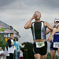 Nederland.Almere Haven.27 augustus 2005.<br /> Tijdens de Holland Triathlon in Almere Haven waren er verschillende waterposten voor de tri-athlon atleten.Dorst lessen.Conditie.Marathon.Atletiek.Hardlopen.Sport.Sportief.Sportkleding.Waterstop.<br /> Participants in the Holland Triathlon 2005.