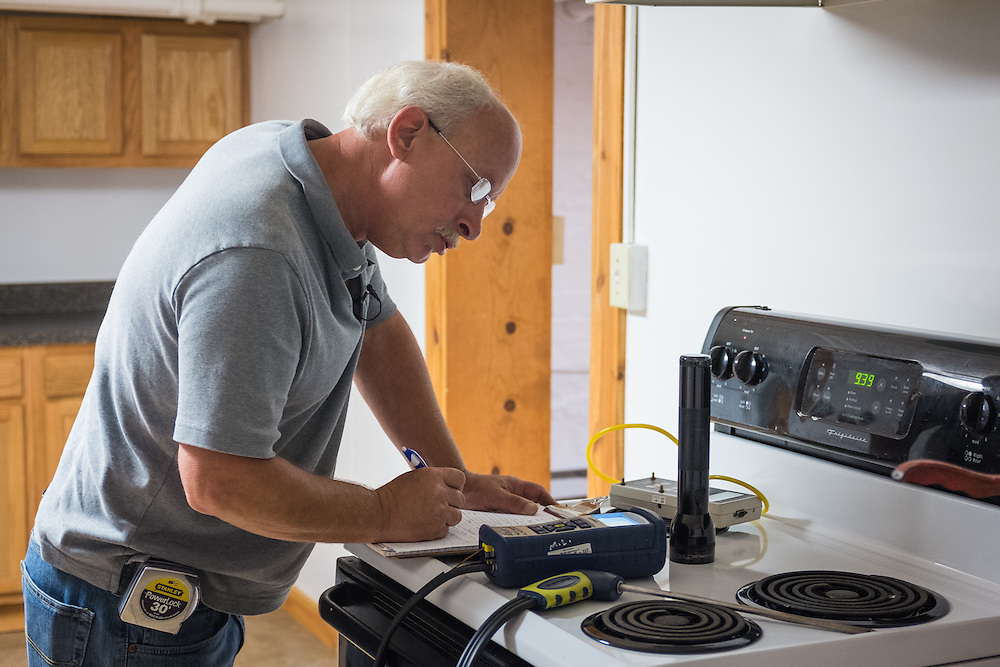 Mike Lehman from the Coporation for Appalachian Development (COAD) records his findings during an energy audit at 86 West State Street  on Wednesday, June 24, 2015.  Photo by Ohio University  /  Rob Hardin