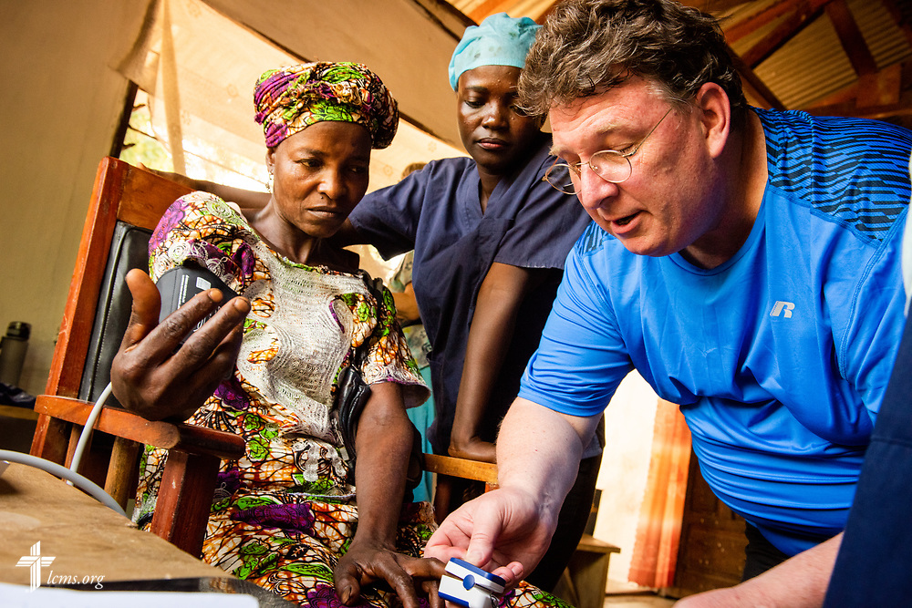 The Rev. Michael Awe, team leader and pastor at Hope Lutheran Church, South Sioux City, Neb., works with Rugiatu Kamande, a nurse from Sierra Leone, as they take vitals from a patient during the second day of the LCMS Mercy Medical Team on Tuesday, May 8, 2018, in the Yardu village outside Koidu, Sierra Leone, West Africa. LCMS Communications/Erik M. Lunsford