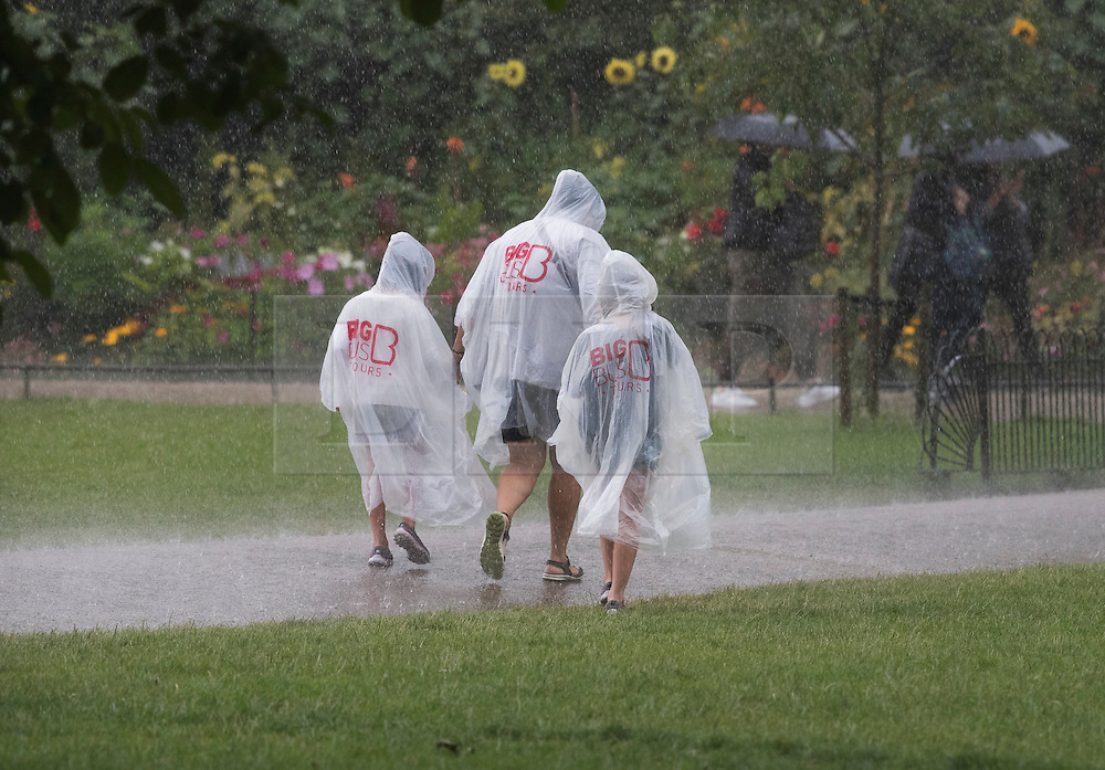 © Licensed to London News Pictures. 12/07/2016. London, UK. A family wear waterproof macs in St James' Park as a sudden rain storm hits central London. Photo credit: Peter Macdiarmid/LNP