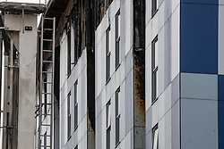 "© Licensed to London News Pictures. 16/11/2019. Bolton, UK. Molten cladding is visible at the site of the blaze . Firefighters work at the scene where a fire broke out overnight (15th/16th November 2019) at a block of flats known as "" The Cube "" , in Bolton Town Centre . At least two people are known to have been treated by paramedics at the scene of the six-story block , which is occupied by students of the University of Bolton . Photo credit: Joel Goodman/LNP"