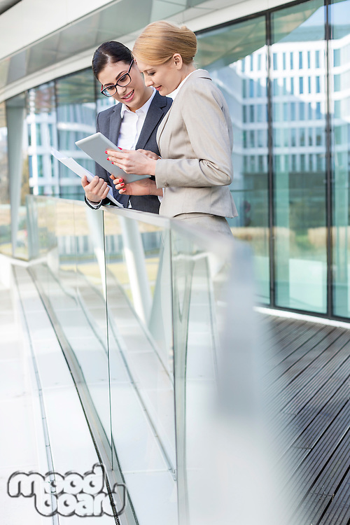 Businesswomen using digital tablet by glass railing