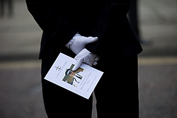 © Licensed to London News Pictures . 02/11/2015 . Liverpool , UK . A police officer in dress uniform clutching a copy of the order of service at the funeral of Police Constable Dave Phillips , at Liverpool Cathedral . Five people are charged in connection with his death , including Clayton Williams , 18 , from Wallasey , who is charged with murder . Photo credit: Joel Goodman/LNP