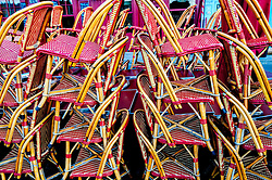 Chairs stacked out side a cafe at the harbour in Honfleur, Normandy, France