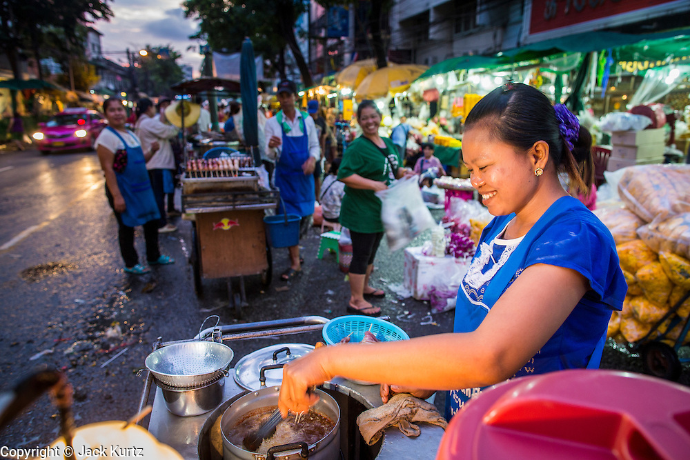 09 OCTOBER 2012 - BANGKOK, THAILAND: A street food vendor fries some meat in front of the Bangkok Flower Market. The Bangkok Flower Market (Pak Klong Talad) is the biggest wholesale and retail fresh flower market in Bangkok. It is also one of the largest fresh fruit and produce markets in the city. The market is located in the old part of the city, south of Wat Po (Temple of the Reclining Buddha) and the Grand Palace.    PHOTO BY JACK KURTZ