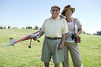 Senior couple standing on field, man holding model plane