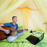 Nederland, Rotterdam, 12 juni 2017.<br /> Kinderboekenschrijver, scenarioschrijver, auteur, Benny Lindelauf wordt wakker met het spelen van gitaarliedjes die hij op de computer heeft staan.<br /> <br /> Foto: Jean-Pierre Jans